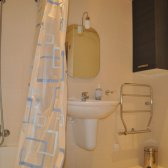 Second bathroom with bathtub and shower curtain